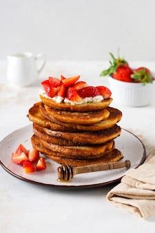 Stos francuskich tostów z twarogiem, miodem i truskawkami na śniadanie. selektywne skupienie
