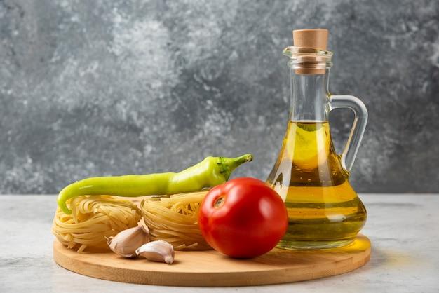 Stos gniazd surowego makaronu, butelka oliwy z oliwek i warzywa na białym stole.