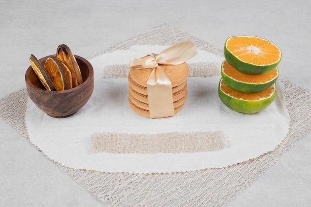 Stos herbatników związanych z kokardą i plasterkami mandarynki na tle marmuru. wysokiej jakości zdjęcie