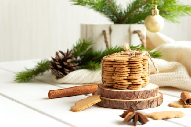Stos imbirowych ciasteczek i przypraw na drewnianym blacie