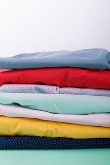 Stos jasnych kobiecych spodni. złożone kolorowe spodnie i dżinsy. ścieśniać