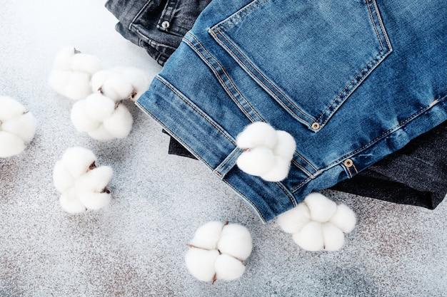 Stos jeansów spodnie i bawełniane kwiaty na światło