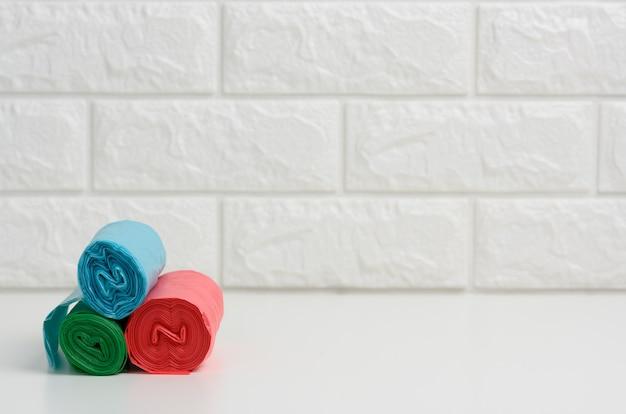 Stos jednorazowych plastikowych worków na śmieci na białym stole, tle ściany z cegły, kopia przestrzeń