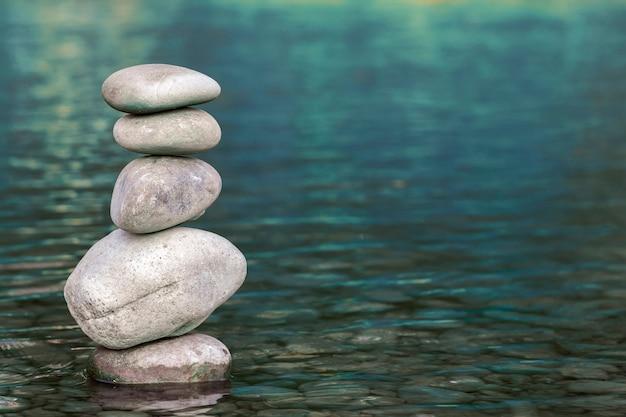 Stos kamieni równoważenia na górze w błękitne wody rzeki