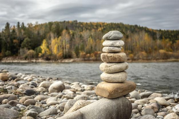 Stos kamieni zbudowany w kopcu na tle rzeki. spokój i oderwanie od natury