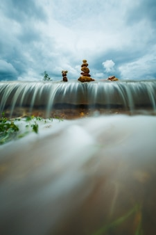 Stos kamieni zen nad wodospadem na tle burzy chmur