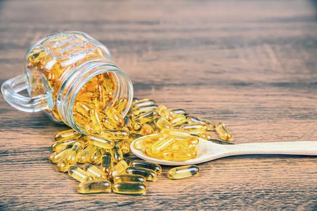 Stos kapsułki oleju z wątroby dorsza na stole.
