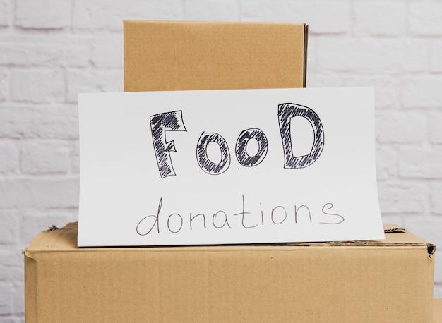 Stos kartonów i białej kartki papieru z napisem darowizny żywności na tle białej cegły ściany