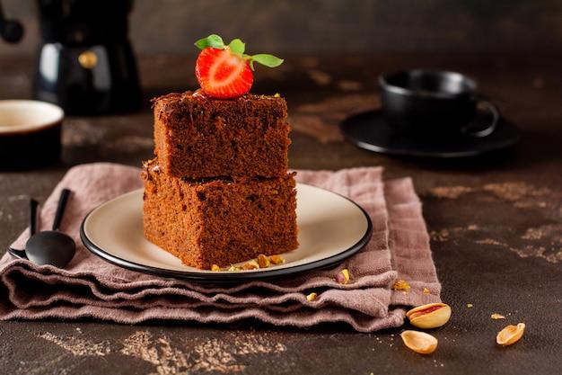 Stos kawałków lub batonika brownie ciasto czekoladowe z truskawkami i orzechami pistacjowymi na czarnej powierzchni, selektywny obraz ostrości.