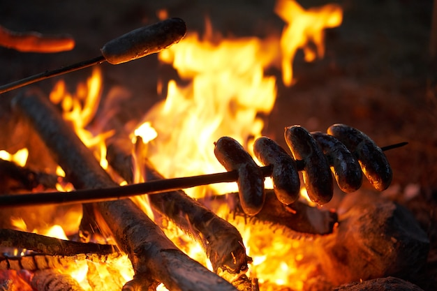 Stos kiełbasek na patyczkach smażonych na ognisku