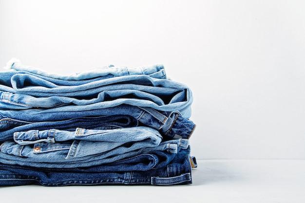 Stos klasycznych niebieskich dżinsów na jasnej ścianie. miejski strój, podstawowa niezbędna garderoba, pomysł na zakupy