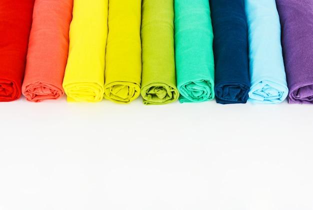 Stos kolorowe t-shirt zwinięte na białym tle