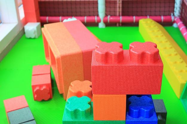 Stos kolorowi duzi bloki buduje zabawki pieni się. plac zabaw dla dzieci w wieku przedszkolnym.