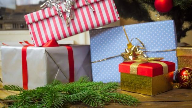 Stos kolorowych prezentów ze wstążkami pod choinką