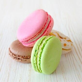 Stos kolorowych tradycyjnych francuskich makaroników deserowych na białym drewnianym stole.