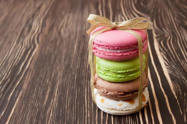 Stos kolorowych tradycyjnych francuskich makaroników deserowych ze złotą kokardą na brązowym drewnianym stole.