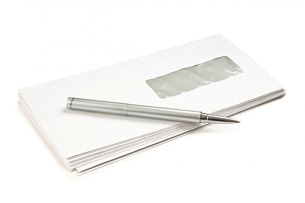 Stos kopert pocztowych i długopis na białym tle