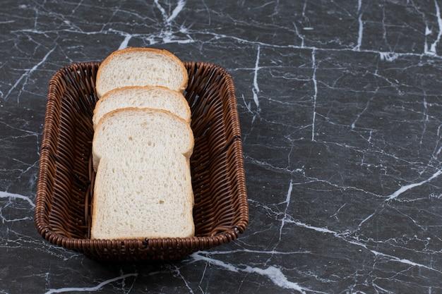 Stos kromek białego chleba w koszyku.