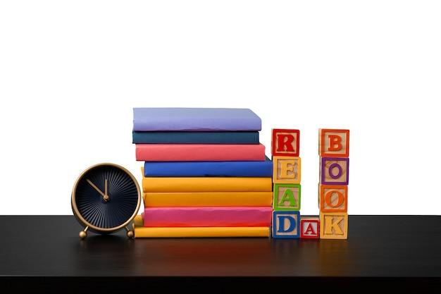 Stos książek i czas budzika na przeczytanie koncepcji