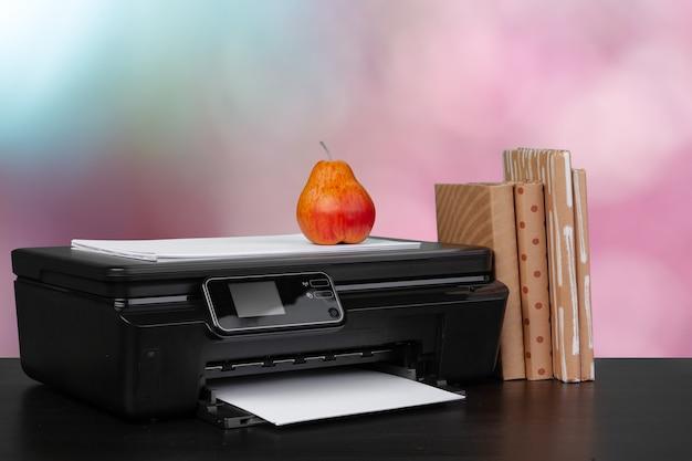 Stos książek i domowa drukarka na rozmytym tle