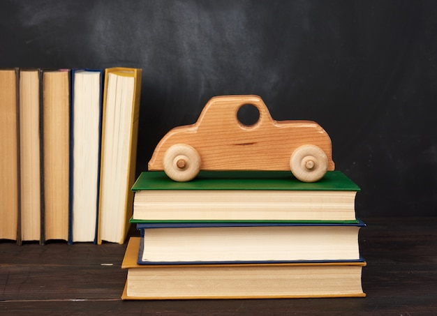 Stos książek i drewniany samochodzik na kółkach, przestrzeń z czarnej tablicy kredą