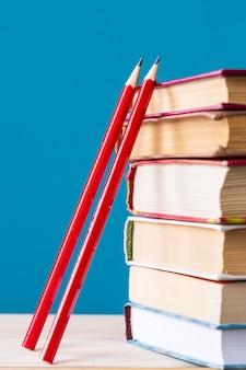 Stos książek i dwa czerwone drewniane ołówki na niebieskim, z powrotem do szkoły