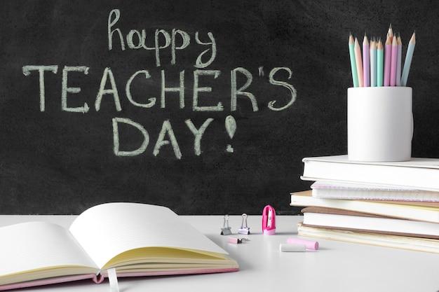 Stos książek i ołówków koncepcja szczęśliwy dzień nauczyciela