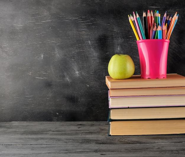 Stos książek i wielobarwne drewniane ołówki