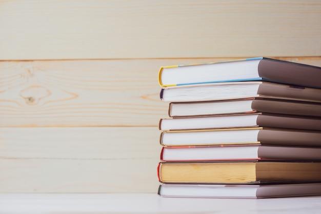Stos książek leżących na stole na jasnym tle drewnianych. powrót do szkoły. wykształcenie.