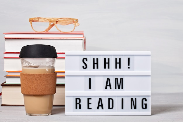 Stos książek, lightbox z tekstem, filiżanka kawy