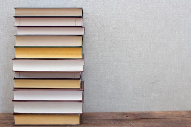 Stos książek na drewnianej półce i szary