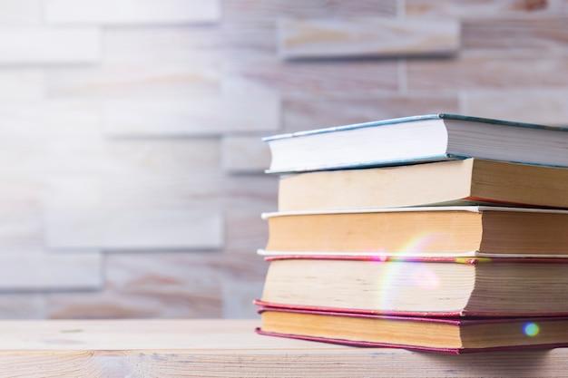 Stos książek na drewnianym biurku. powrót do szkoły. samokształcenie