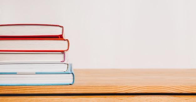 Stos książek na drewnianym stole. makieta z koncepcją edukacji i czytania. literatura do nauki, rozwoju i radości