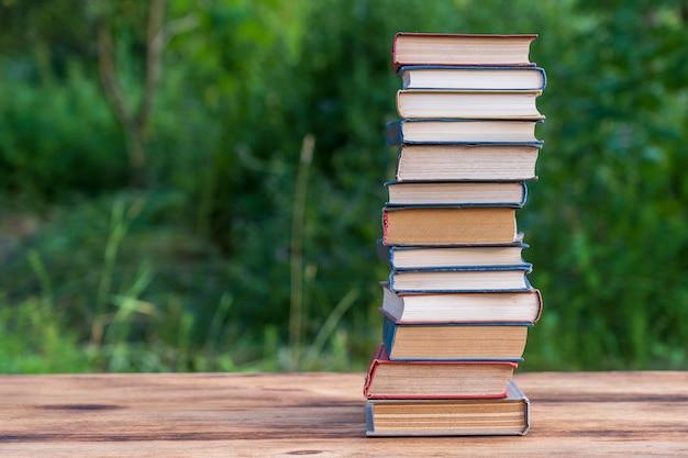 Stos książek na drewnianym stole nad naturą