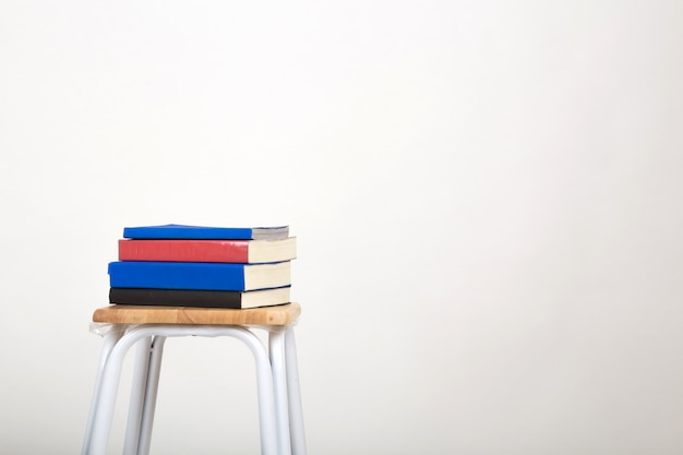 Stos książek na krześle. pojedyncze białe tło.