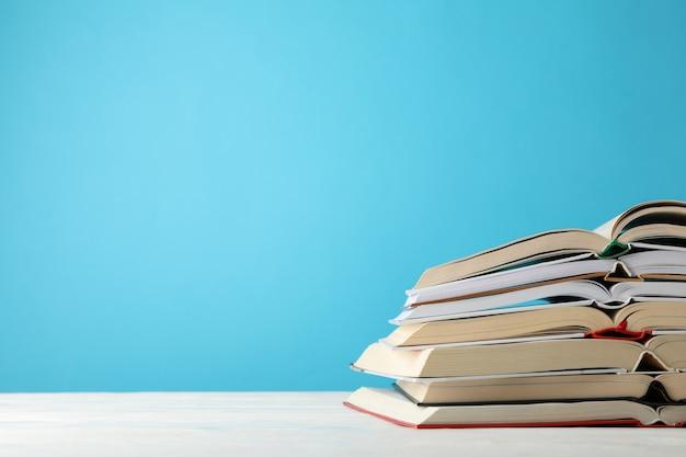 Stos książek na tle niebieskiej przestrzeni, miejsca na tekst