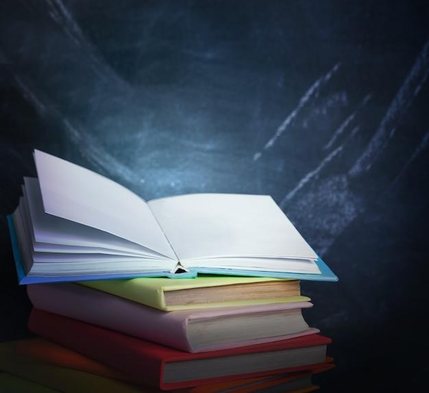 Stos książek na tle tablicy nauczycielskiej