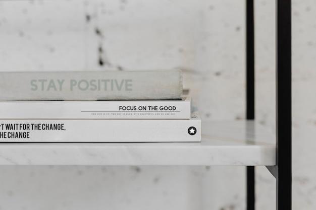 Stos książek psychologicznych na białej marmurowej półce