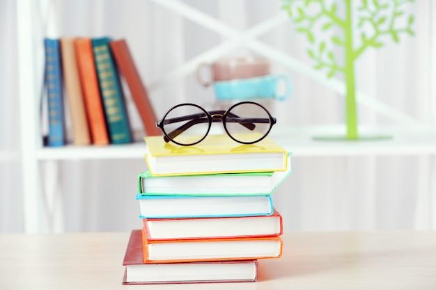 Stos książek w okularach na drewnianym stole w pokoju
