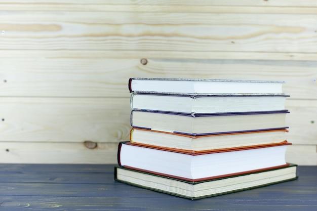 Stos książek w twardej oprawie na drewnianym stole. powrót do szkoły