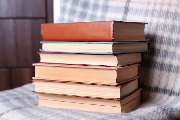 Stos książek z ciepłą kratą na krześle