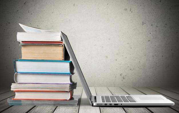 Stos książek z laptopem na stole