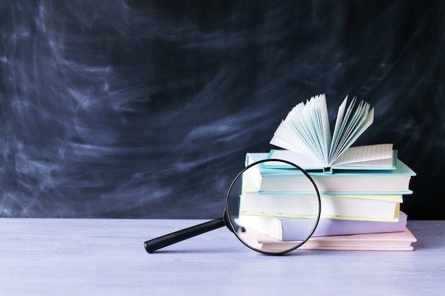 Stos książek z lupą na stole i ciemnoniebieskim tle