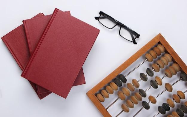 Stos książek z rocznika liczydło i okulary na białym tle