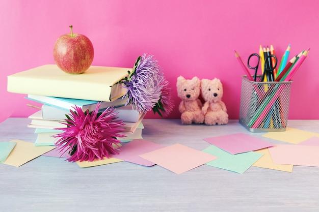 Stos książek z zakładkami ze świeżych kwiatów jabłko pluszowe misie ołówki papier powrót do szkoły