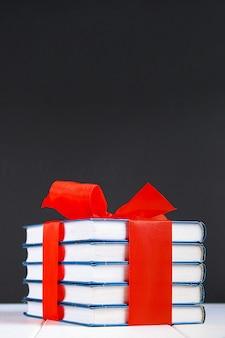Stos książek związany z czerwoną wstążką na białym drewnianym stole.