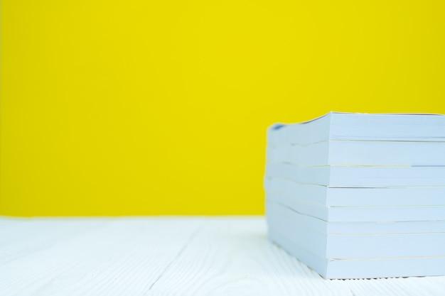 Stos książka na bielu stole z żółtym tłem.