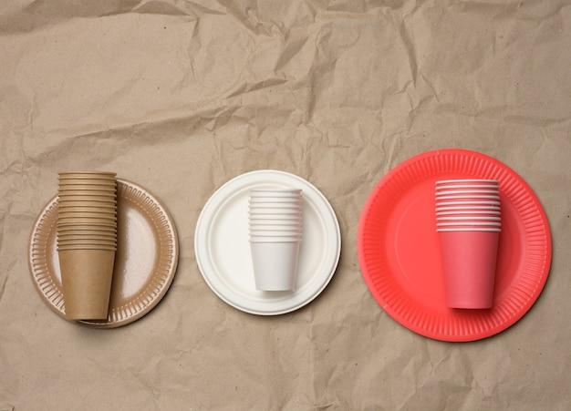 Stos kubków papierowych i okrągłych talerzy na tle brązowego papieru. koncepcja odrzucenia plastiku, zero odpadów