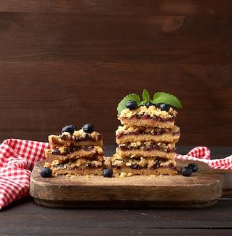 Stos kwadratowe plastry pieczone ciasto z kruszonką z niebieską śliwką na drewnianej desce