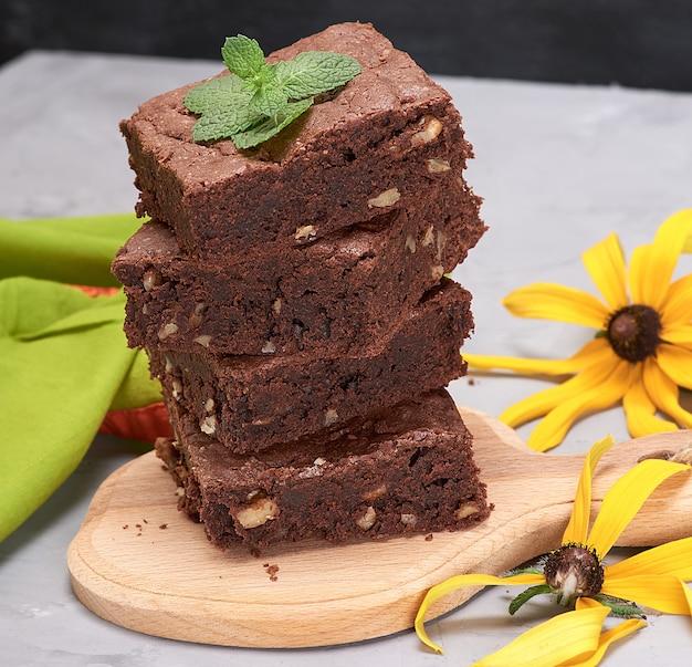 Stos kwadratowych kawałków ciasto czekoladowe brownie z orzechami